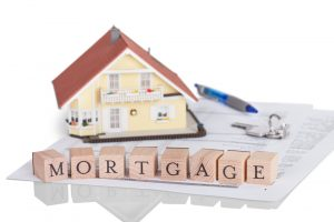 Small playhouse sitting on mortgage documents along with pen, house keys and the letters for mortgage spelled out on the face of blocks